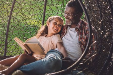girl and granddad reading book
