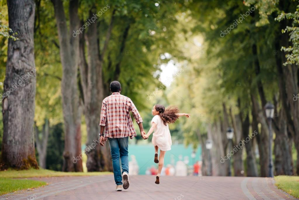 girl walking with grandfather in park