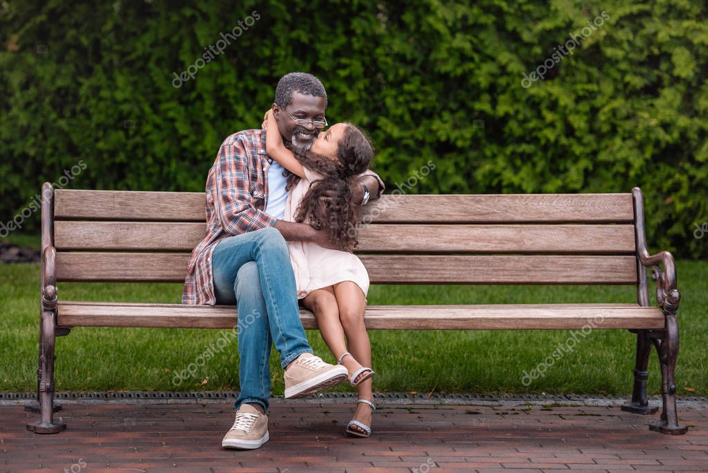 girl hugging and kissing her grandfather