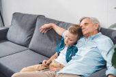 grandfather and grandson sleeping on sofa