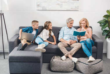 family with book and laptop