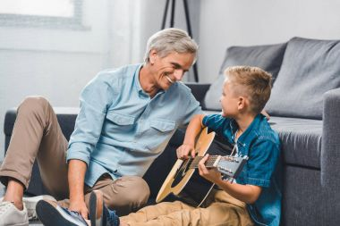 grandfather and grandson playing on guitar