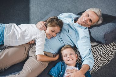Grandfather and grandchildren lying on floor