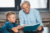 Fotografie grandfather and grandson reading book