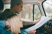 Fotografie couple of travelers with map in minivan