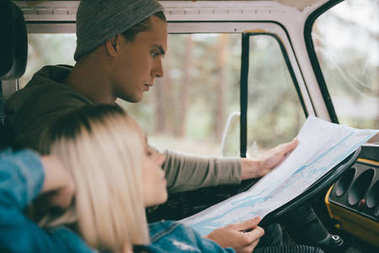 couple of travelers with map in minivan