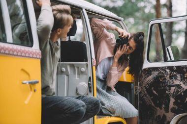 Girlfriend taking photo of her boyfriend on camera while sitting in retro styled minivan stock vector