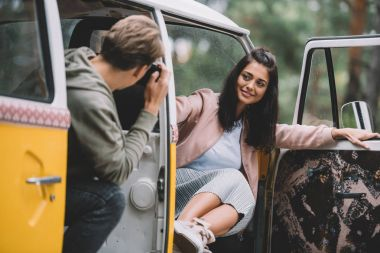 Boyfriend taking photo of his happy girlfriend on camera while sitting in retro styled minivan stock vector