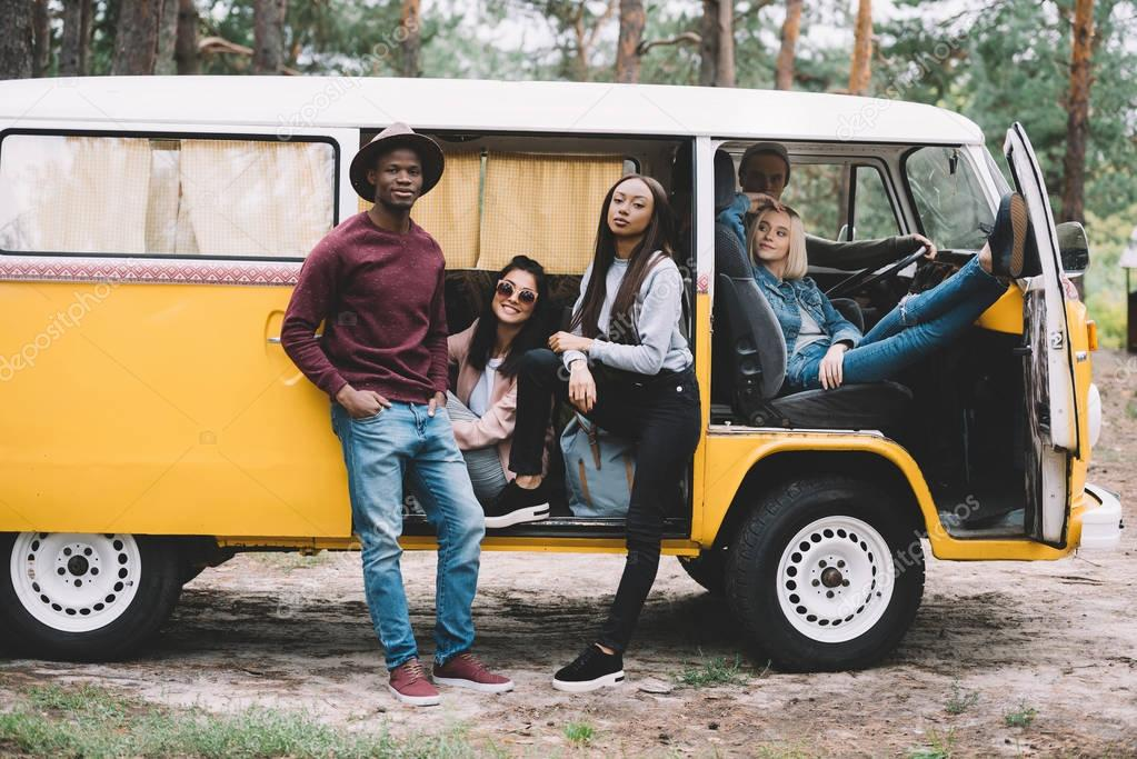 multiethnic friends traveling in minivan