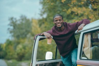 Afro man with coffee in minivan