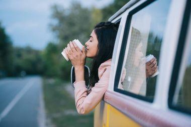 girl with coffee in retro minivan