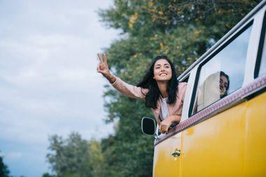 Girl with peace symbol in minivan