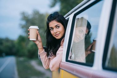 traveler with coffee in retro minivan