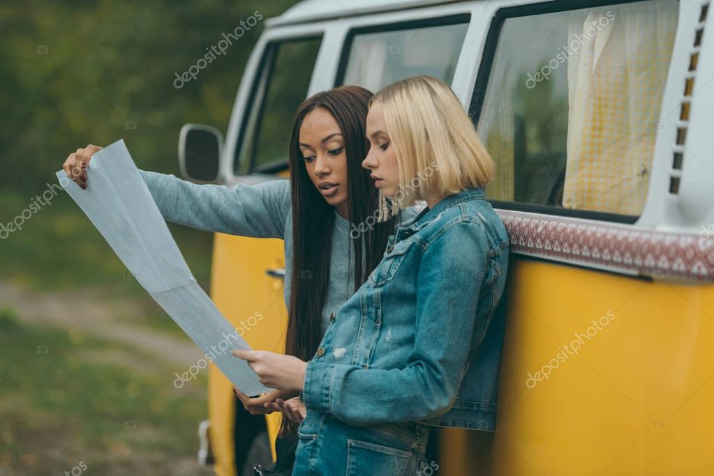 multiethnic girls looking at map