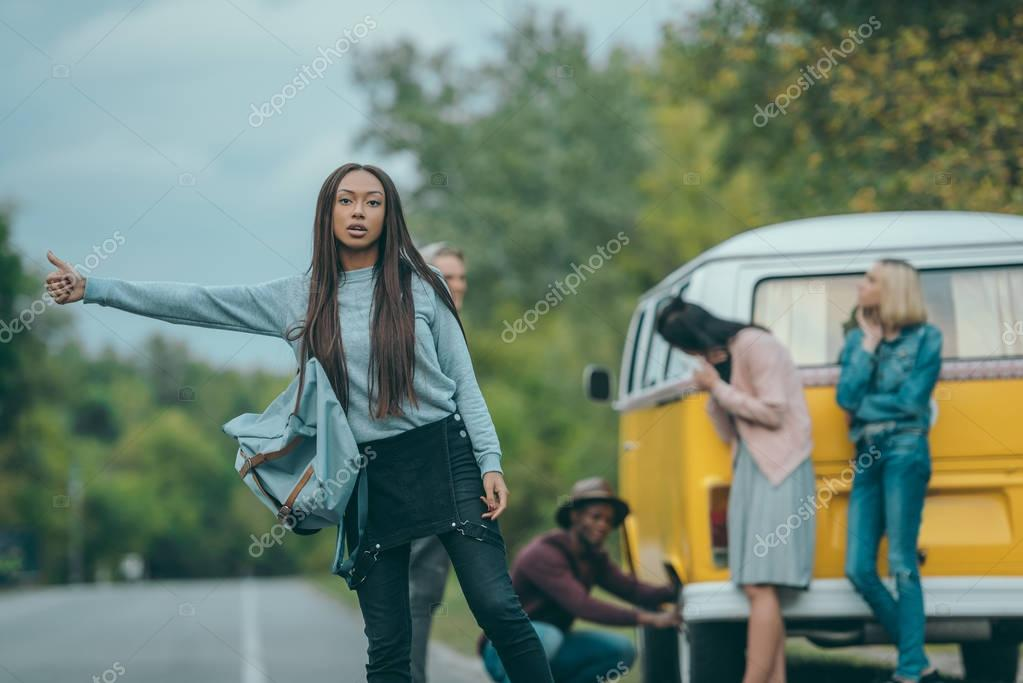 african american girl hitchhiking on road