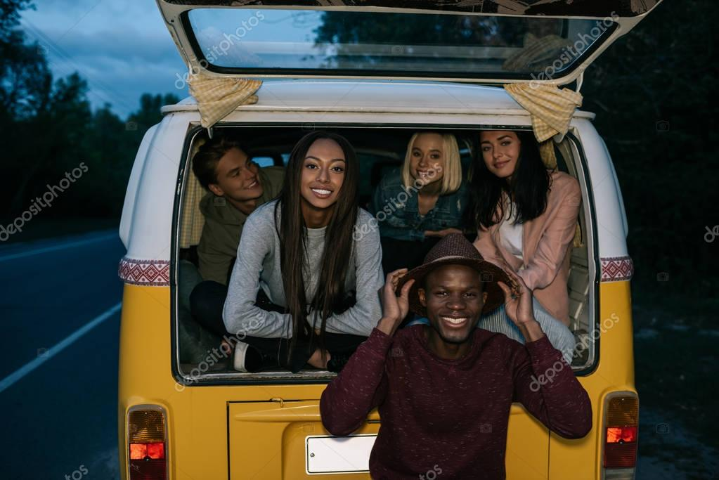 multiethnic friends traveling on minivan