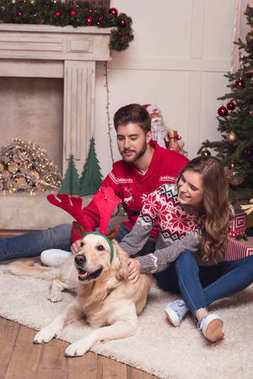 couple with dog at christmastime