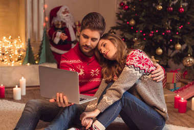 couple with laptop at christmastime