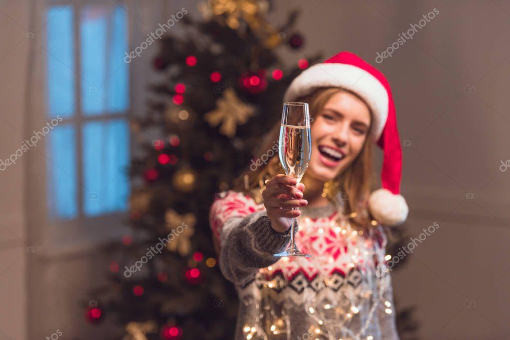 girl in santa hat drinking champagne