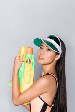 woman in swimsuit and visor with water gun