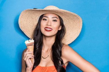 Smiling asian woman in beach attire holding an ice-cream cone and looking at camera stock vector