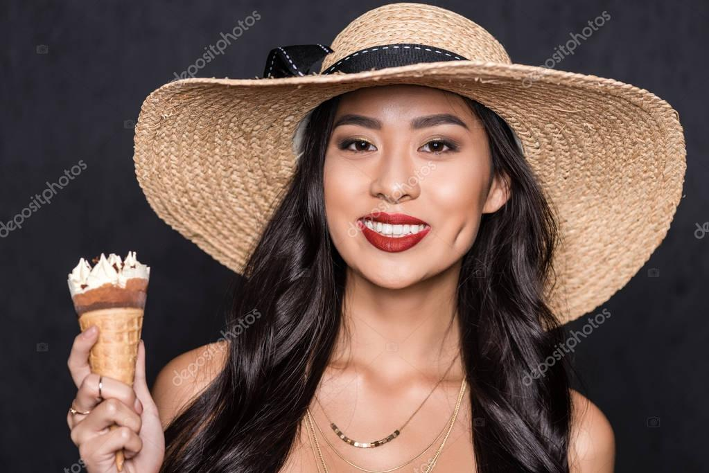 woman in beach hat holding ice-cream