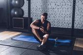 Sportlicher Mann blickt auf Smartwatch