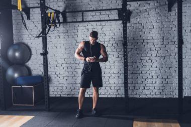 Athletic man using smartphone
