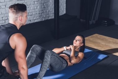 woman doing abs exercises with trainer