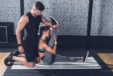 trainer helping woman to stretch