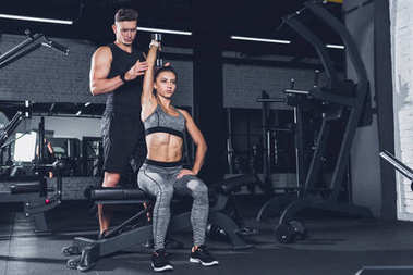trainer helping woman to exercise with dumbbell
