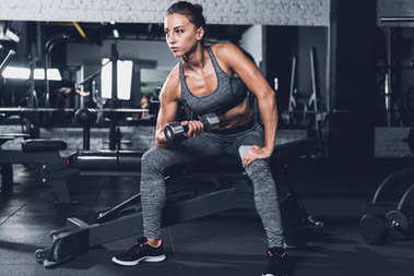Sportive woman exercising with dumbbell
