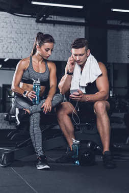 sportive couple with smartphone