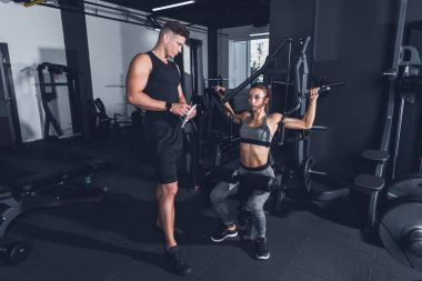 trainer and sportive woman in gym