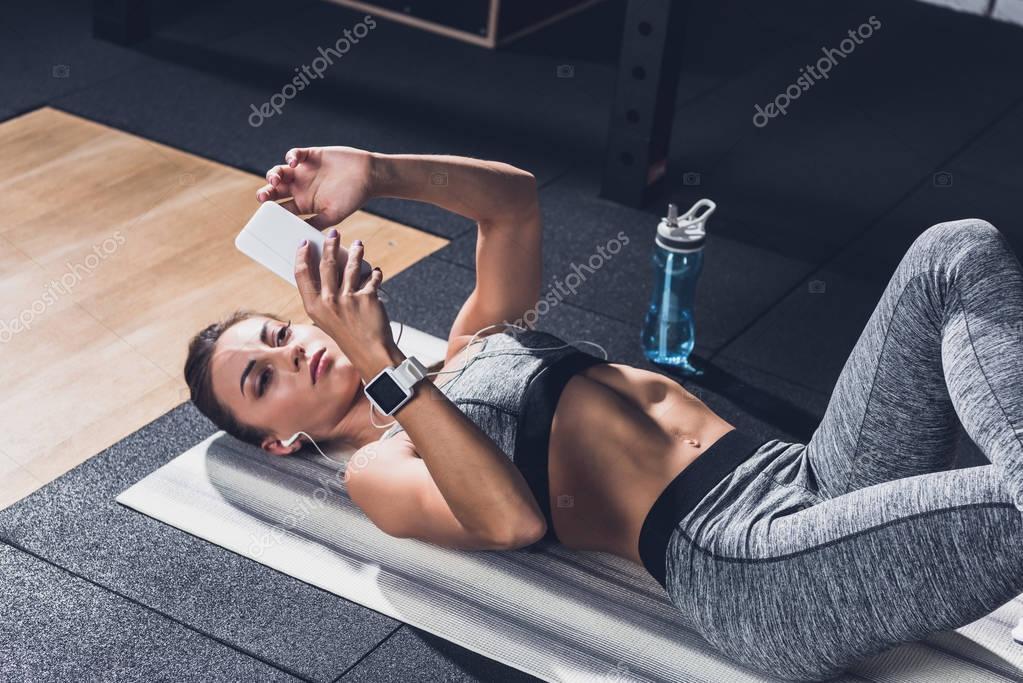 sportive woman using smartphone