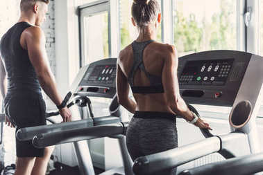 couple exercising on treadmills