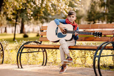 Little boy with guitar in park