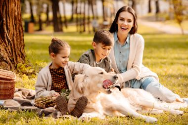 Children and mother petting dog in park