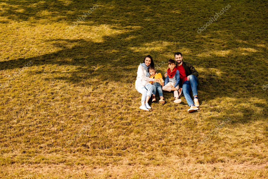 Family sitting on grassy hill