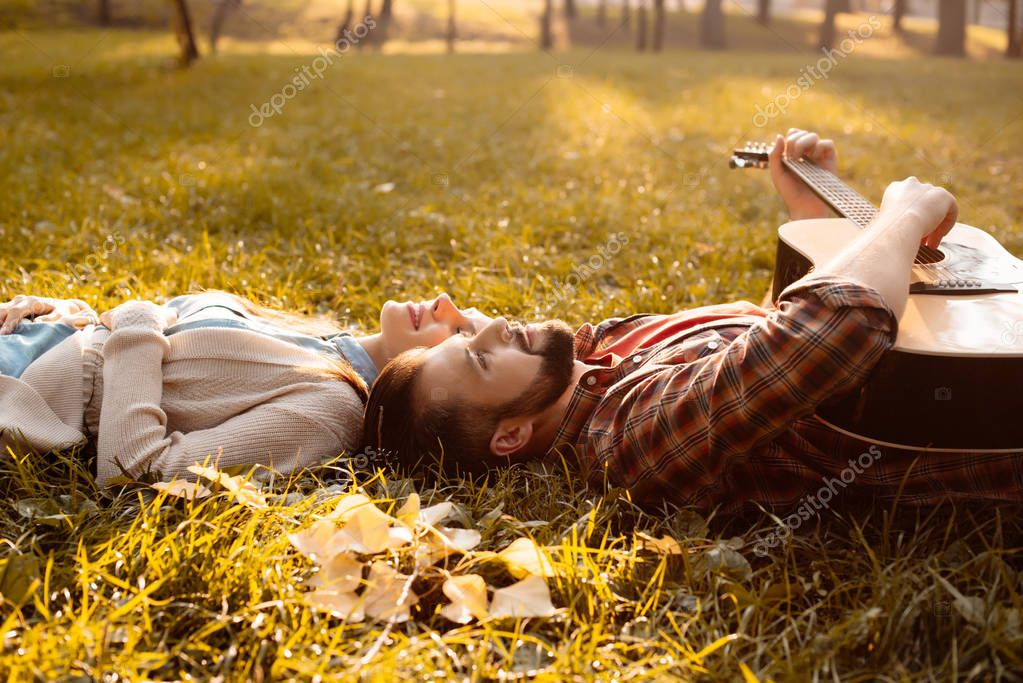 Couple lying on grass with guitar