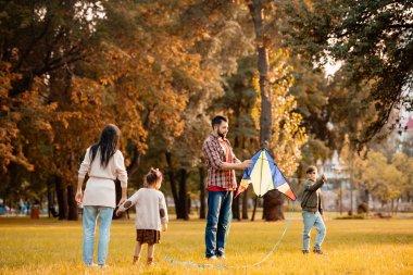 Family flying kite in park