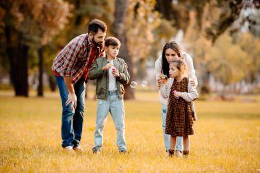 Family blowing soap bubbles