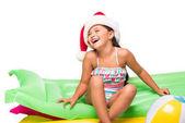 Kind in Weihnachtsmütze auf Matratzen schwimmen