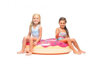 kids sitting on swim tube