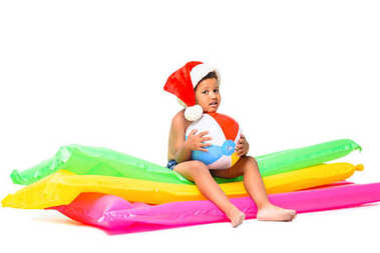 boy in santa hat on swimming mattresses
