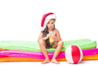 kid in swimsuit and santa hat with juice