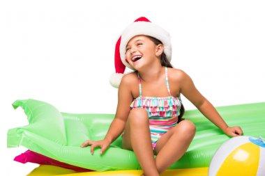 child in santa hat on swimming mattresses