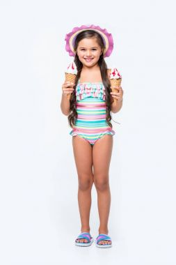Cute little girl in swimsuit holding ice cream and smiling at camera stock vector