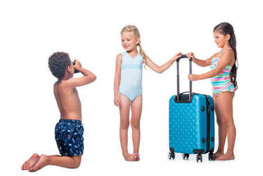 African american boy kneeling and photographing happy little girls with suitcase isolated on white stock vector