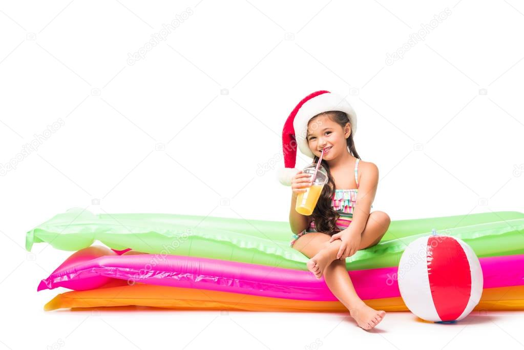 kid in santa hat with orange juice